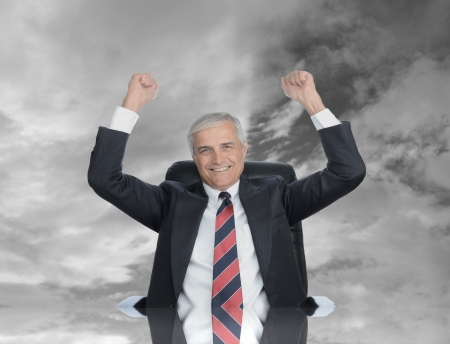 puños cerrados: Hombre de negocios sentado en su escritorio con los puños en el aire a la celebración de un acuerdo cerrado. Cielo de fondo con refelction en la parte superior del escritorio. Foto de archivo