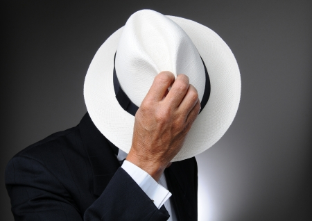 Man in a tuxedo hidind behing his hat. Horizontal closeup over a gray background.