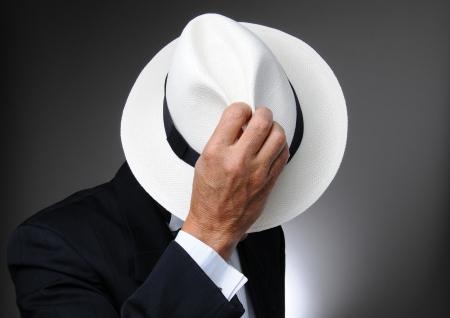 L'homme en smoking hidind behing son chapeau. Gros plan horizontal sur un fond gris.