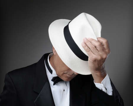 obscured: Closeup of a middle aged man wearing a tuxedo and a Panama Hat. Horizontal over a gray background.