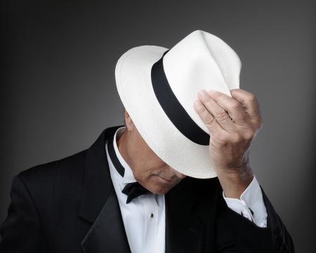 hombre con sombrero: Primer plano de un hombre de mediana edad que llevaba un esmoquin y un sombrero de Panamá. Horizontal sobre un fondo gris. Foto de archivo