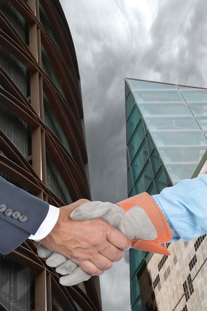 Closeup of a manager and laborer shaking hands in front of two modern buildings. Vertical format. Фото со стока