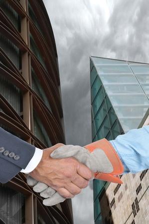 obrero: Primer plano de un gerente y el trabajador apret�n de manos delante de dos edificios modernos. Formato vertical.
