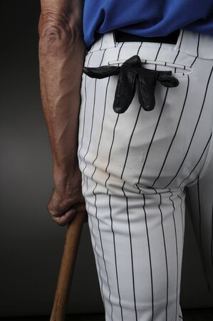 pinstripes: Closeup of a baseball player seen from behind and leaning on a wood bat. Man is unrecognizable with a batting glove in his pocket. Vertical format over a light to dark background. Stock Photo