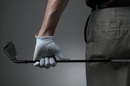 자신의 몸 뒤에 아이언 6 개를 들고 남성 골퍼의 근접 촬영입니다. 남자가 자신의 손에 골프 장갑이 있습니다. 어두운 회색 배경에 빛 위에 가로 형식입 스톡 콘텐츠