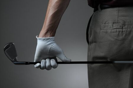 Closeup of a male golfer holding a six iron behind his body. Man has a Golf Glove on his hand. Horizontal format over a light to dark gray background. photo