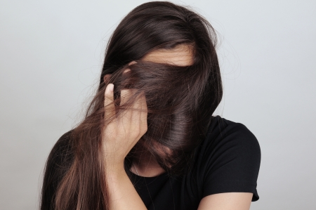 pulling hair: Portrait of a young woman pulling her long brown hair across her face. Female is unrecognizable. Stock Photo
