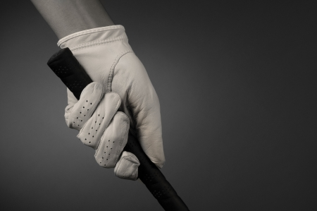 hand grip: Closeup of a golfers hand on the handle of a golf club. Horizontal format on a light ot dark background. Slight sepia toning for an old fashioned look.