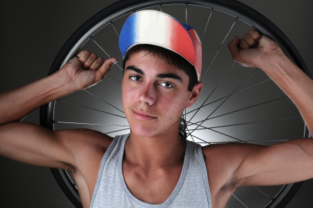 Portrait of a teenage cyclist holding a wheel behind his head. Closeup in horizontal format with a gray light ot dark background. photo