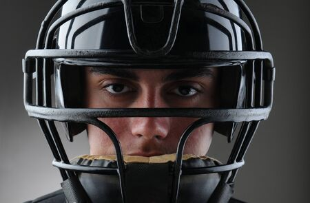 protective mask: Closeup of a male baseball catcher with his protective mask on. Horizontal format with a light to dark gray background. Stock Photo
