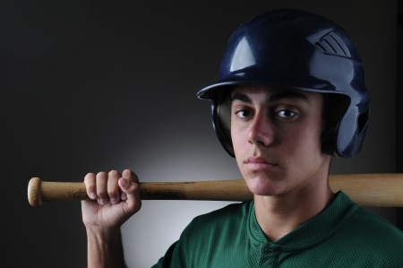 Closeup of a Teenage baseball player holding a bat on his shoulder. Horizontal format with a light to dark gray background. photo