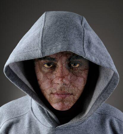 A zombie like teenage male in a gray hoodie.