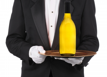 Butler wearing a tuxedo holding a bottle of Chardonnay Wine on a serving tray. Horizontal format showing persons torso only. photo