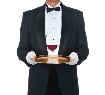 sirvientes: Camarero Tuxedo uso de bandeja con un vaso de vino tinto. Formato cuadrado sobre un fondo blanco. Foto de archivo
