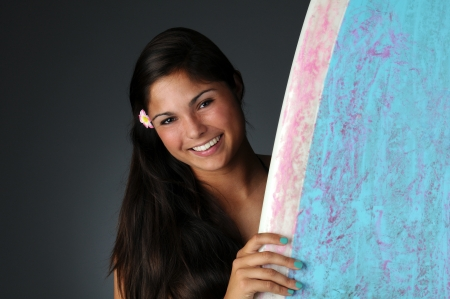 Portrait of a teenage surfer girl peeking out from behind her surfboard. Horizontal format over a light to dark gray background. Stock Photo - 14505644