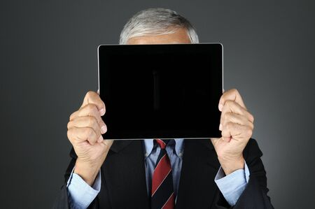 blank tablet: Closeup of a businessman holding his tablet computer with blank screen in front of his face.. Horizontal format over a light to dark gray background. Man is unrecognizable.