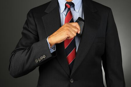 breast pocket: Closeup of a businessman reaching into his coat pocket to get his wallet Stock Photo