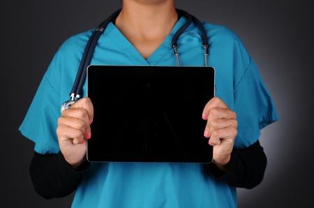 blank tablet: Closeup of a nurse holding a tablet computer with a blank black screen in front of hers torso.  Horizontal format over a light to dark gray background. Woman is unrecognizable.