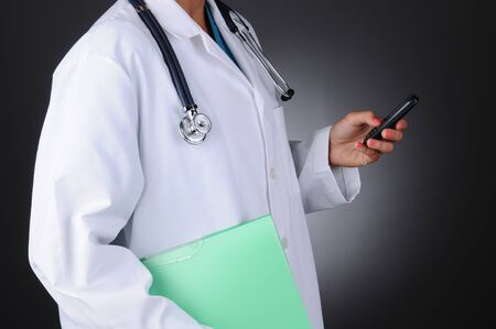 Closeup of a nurse holding a chart in one hand abd her cell phone in the other.  Horizontal format over a light to dark gray background. Woman is unrecognizable. photo