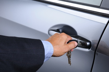 lock and key: Closeup of a mans hand inserting a key into the door lock of a car  Horizontal format  Car and man are unrecognizable