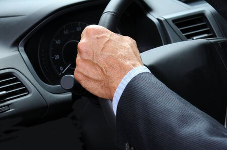 Closeup of a mans hand holding onto the steering wheel of his car  Horizontal format  Car and Driver are unrecognizable  photo