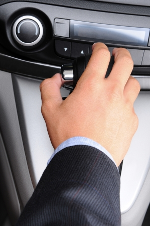 sleeve: Closeup of a mans hand on the gear shifter of his car  Vertical Format  Man and car are unrecognizable  Stock Photo