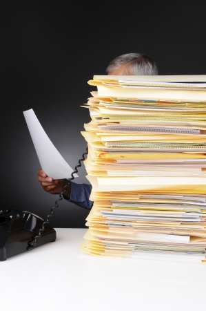 An overworked businessman talking on the telephone hidden behind a large stack of files. Vertical format on a light to dark gray background. Stock Photo - 14668946