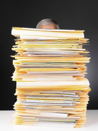 An overworked businessman sitting at his desk hidden behind a large stack of files. Vertical format on a light to dark gray background. Stock Photo - 14671356