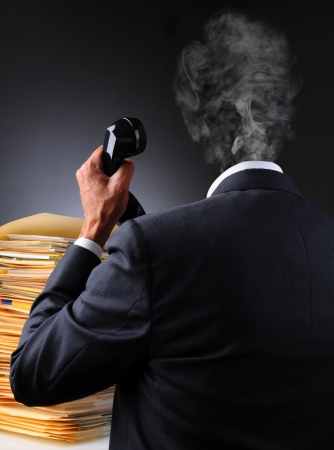 harried: A stressed businessman with files and telephone as his head explodes into a puff of smoke. Vertical format over a dark to light background. Man is unrecognizable.