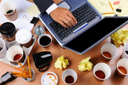 Closeup view of a very cluttered businessmans desk. Overhead view with mans hand on laptop keyboard and scattered coffee cups and office supplies. Horizontal format.