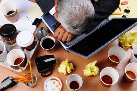 untidy: Closeup view of a very cluttered businessmans desk. Overhead view with mans head on laptop keyboard and scattered coffee cups and office supplies. Horizontal format.
