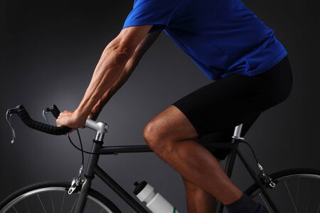 road cycling: Closeup of a man on a road bike iona light to dark gray background. Man is unrecognizable. Side shot in horizontal format showing only top half of bike and mans torso. Stock Photo