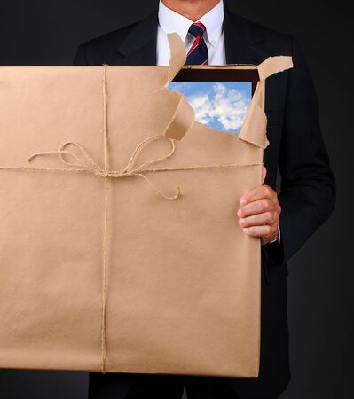 torn: Closeup of a man holding a picture frame wrapped with brown paper in front of his body. Paper is torn revealing one corner with a blue cloudy sky. Stock Photo