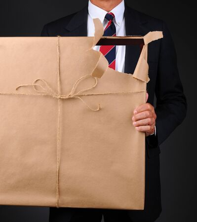 Closeup of a man holding a picture frame wrapped with brown paper in front of his body. Paper is torn revealing as see through hole with the man visible thru the opening.. photo