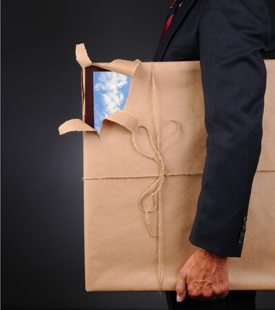 Closeup of a man holding a picture frame wrapped with brown paper under his arm, side view. Paper is torn revealing one corner with a blue cloudy sky.