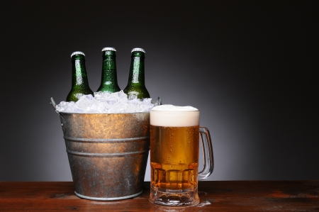 beer bucket: An ice bucket with three green beer bottles next to a full mug of ale on a wet wood surface. Horizontal format with a light to dark gray background.