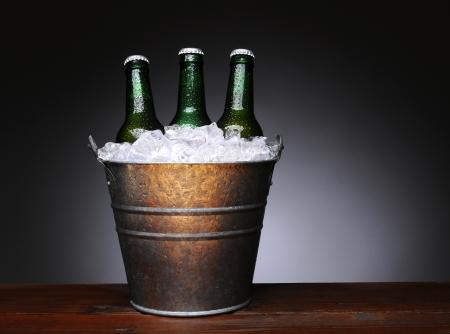 botellas de cerveza: Un cubo de hielo con tres botellas de cerveza verdes en una superficie de madera h�meda. Formato horizontal con una luz de fondo gris oscuro. Foto de archivo