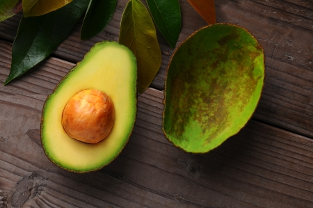 has been: An Avocado cut in half on a wood surface with leaves. One half shows the seed while the other has been scooped out. Stock Photo
