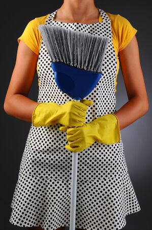 Closeup of a homemaker in an apron holding a broon in front of her torso. Vertical format over a light to dark background. Woman is unrecognizable.  photo