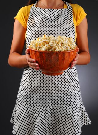 homemaker: Closeup of a homemaker in an apron holding a bowl of popcorn. Vertical format over a light to dark background. Woman is unrecognizable. Shallow depth of field. Stock Photo
