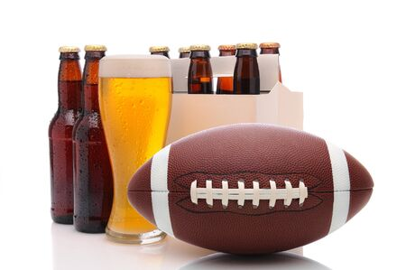 Six pack of beer and frothy glass with an American Football in front. Horizontal format isolated on white with reflection. photo