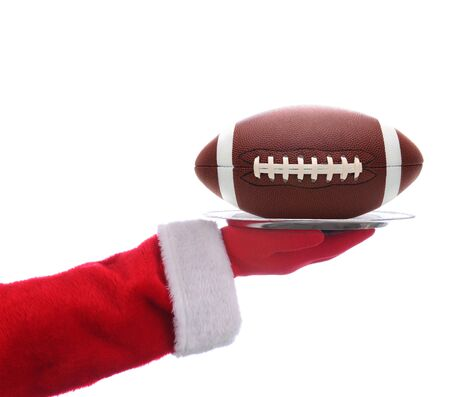 serving tray: Santa Claus outstretched arm holding an American Football on a serving tray. Horizontal format over a white background.