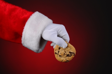 Santa Claus hand holding a chocolate chip cookie over a light to dark red background. Horizontal format showing only hand and arm. Stock Photo - 15097056