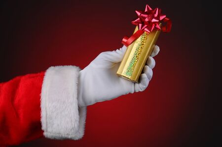 Santa Claus hand holding a wrapped Christmas present over a light to dark red background. Stock Photo - 15097057
