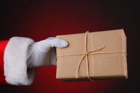 twine: Santa Claus holding a parcel tied with twine over a light to dark red background. Horizontal format showing hand and arm only.