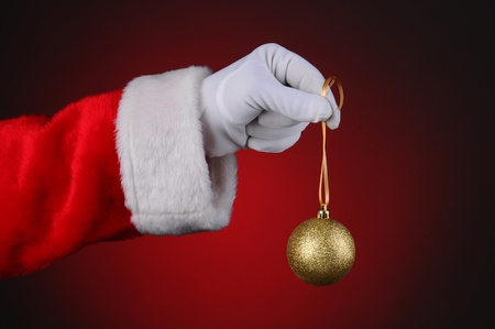 Santa Claus holding a gold sparkly tree ornament over a light to dark red background. Horizontal format showing only hand and arm. Stock Photo