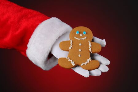 Santa Claus holding a Gingerbread man cookie in the palm of his hand. Horizontal format over a light to dark red background, showing only hand and arm. photo