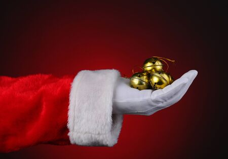 Santa Claus with a handful of gold sleigh bells over a red light ot dark background. Horizontal format showing only hand and arm. photo