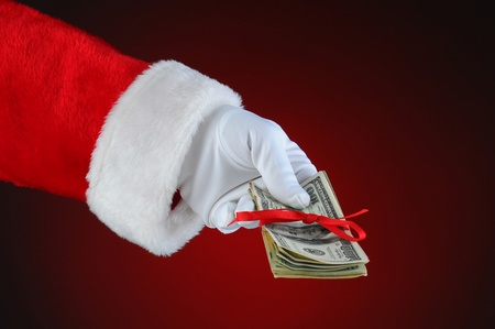 giving hands: Santa Claus hand with cash tied up with a red ribbon  Horizontal format over a light to dark red background