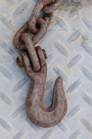 Rusty iron hook and chain laying on an industrial diamond plate surface